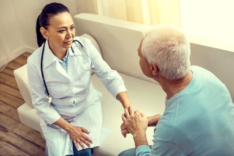 Trabajador médico atento que escucha el paciente mayor agradecido fotos de archivo