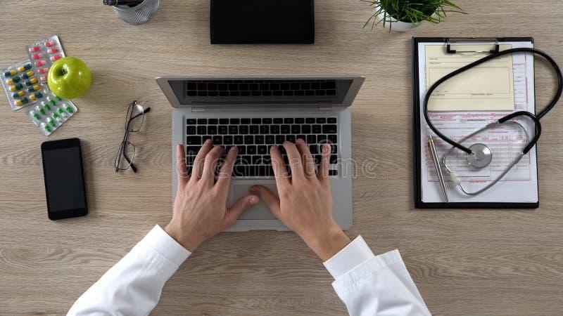 Trabajador médico que mecanografía en el ordenador portátil, guardando informes médicos electrónicos, visión superior foto de archivo