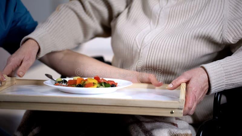 Trabajador m?dico que sirve la ensalada sabrosa al viejo paciente femenino, cuidados de enfermer?a en casa imagen de archivo libre de regalías