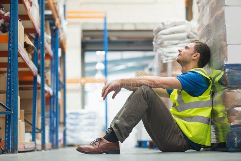 Trabajador manual cansado que se sienta en piso imagenes de archivo