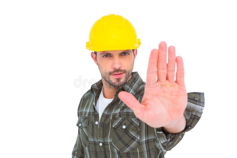 Trabajador manual confiado que gesticula la muestra de la parada fotografía de archivo libre de regalías