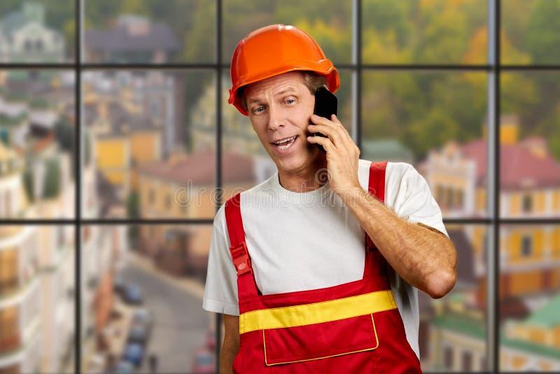 Trabajador manual que habla en el teléfono celular fotos de archivo