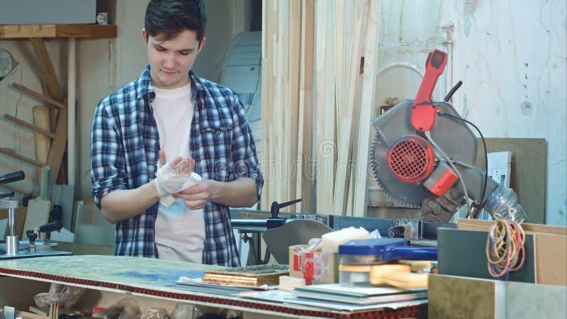 Trabajador manual que venda cuidadosamente su mano herida después de accidente en el lugar de trabajo foto de archivo libre de regalías