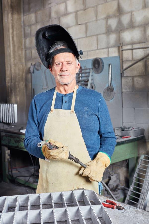 Trabajador mayor de la soldadura en taller foto de archivo