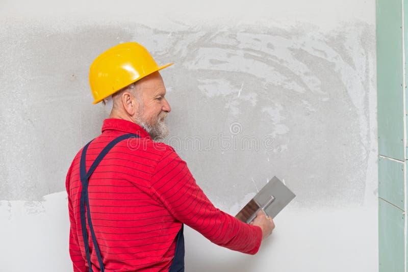 Trabajador mayor que completa las paredes fotografía de archivo