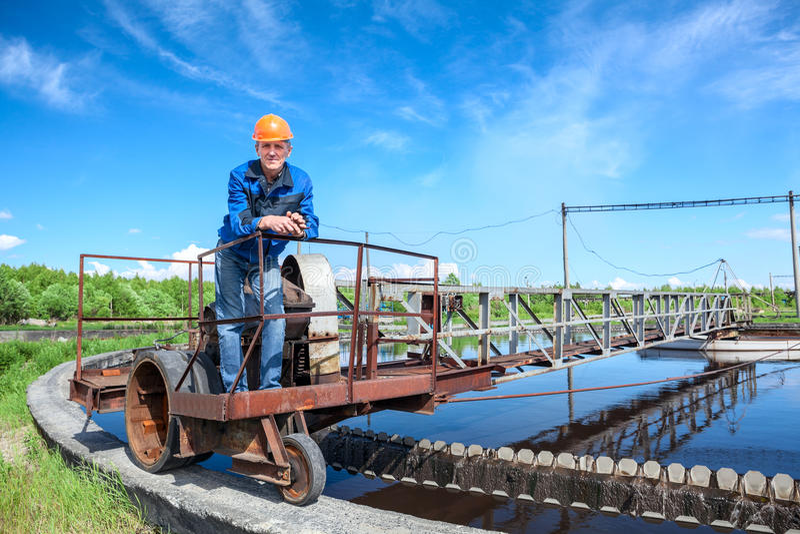 Trabajador mayor que se coloca en unidad del tratamiento de aguas residuales imagenes de archivo