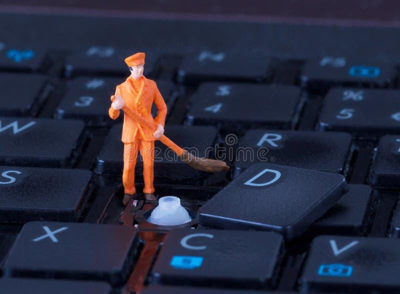 Trabajador miniatura con la escoba que trabaja en el teclado foto de archivo libre de regalías