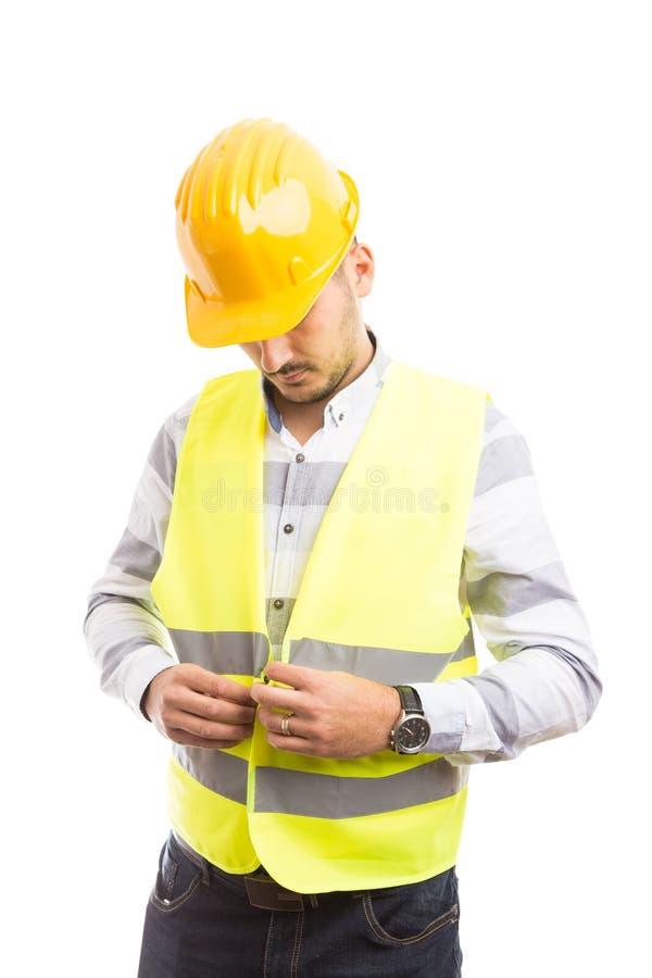 Trabajador o constructor de construcción que se viste para el trabajo fotografía de archivo