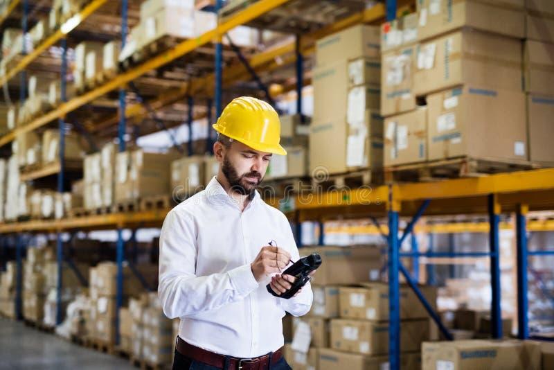 Trabajador o supervisor de Warehouse con el escáner del código de barras foto de archivo libre de regalías