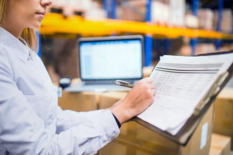 Trabajador o supervisor del almacén de la mujer con el tablero fotografía de archivo libre de regalías