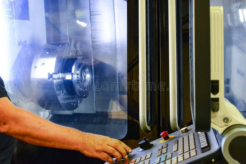 Trabajador, operador del panel de control del programa de la operación de un centro de mecanización de alta precisión del CNC, pr fotografía de archivo libre de regalías