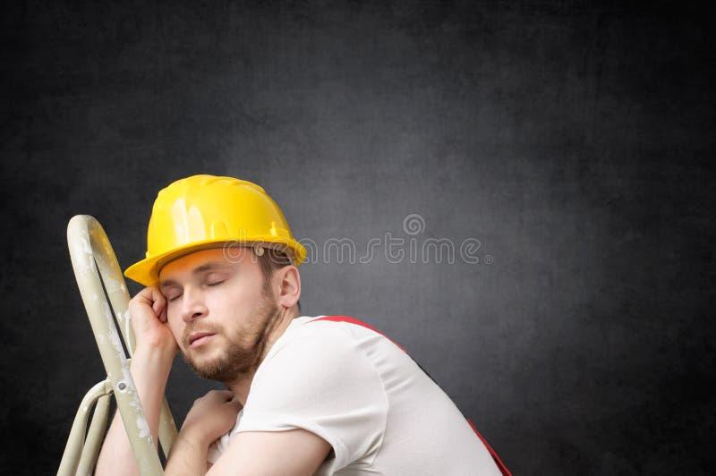 Trabajador perezoso con la escalera foto de archivo