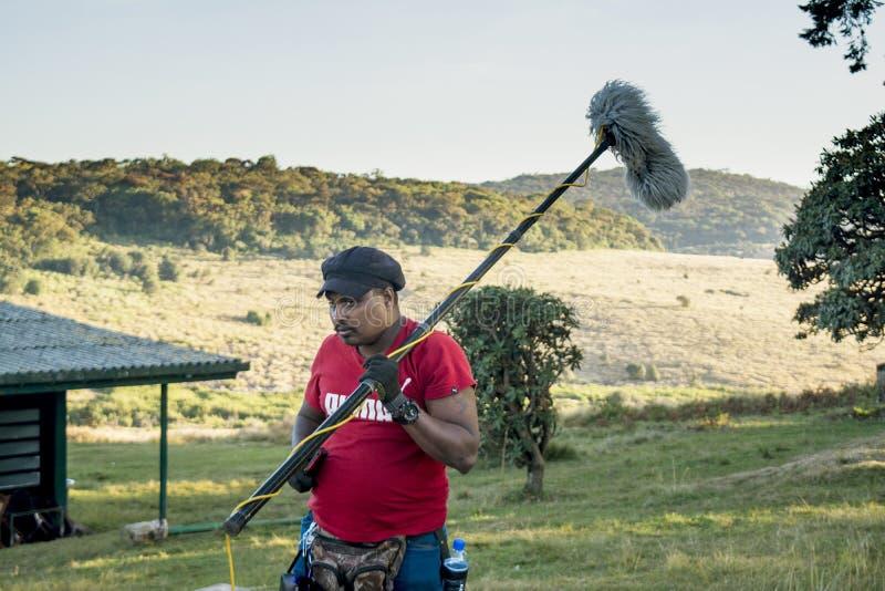 Trabajador que ajusta el micrófono profesional según el tiroteo video documental sobre parque nacional fotos de archivo libres de regalías