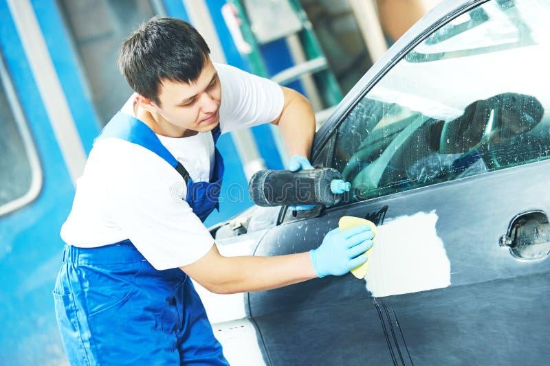Trabajador que aplica el pulimento del coche foto de archivo libre de regalías