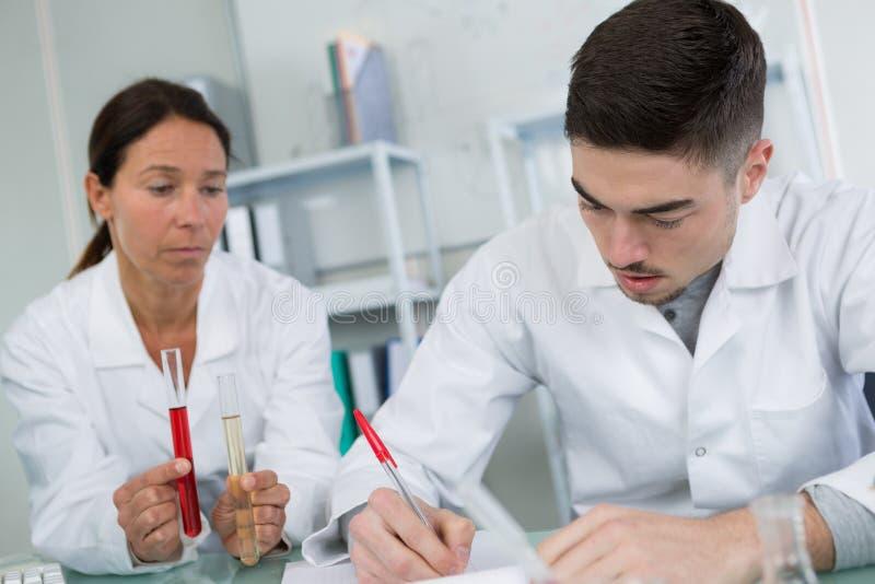 Trabajador que celebra la comprobación de la muestra de sangre y del compañero de trabajo imagen de archivo libre de regalías