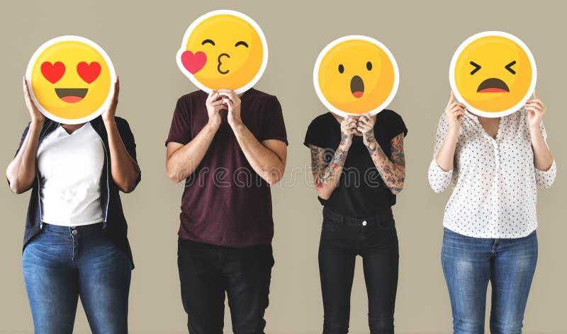 Trabajador que coloca y que sostiene emojis de la cara fotografía de archivo libre de regalías