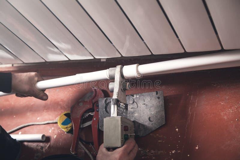 Trabajador que conecta el tubo plástico Instalación del radiador de la calefacción por agua fotos de archivo