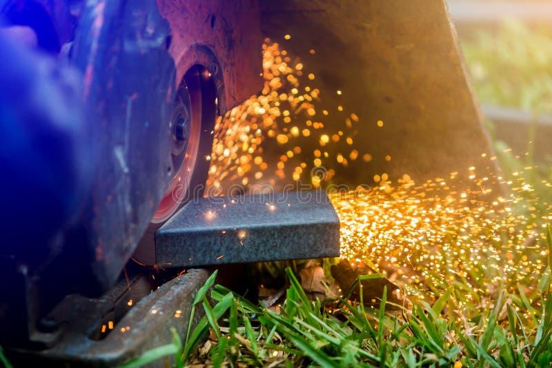 Trabajador que corta el metal con la amoladora en el emplazamiento al aire libre del césped o de la obra fotos de archivo
