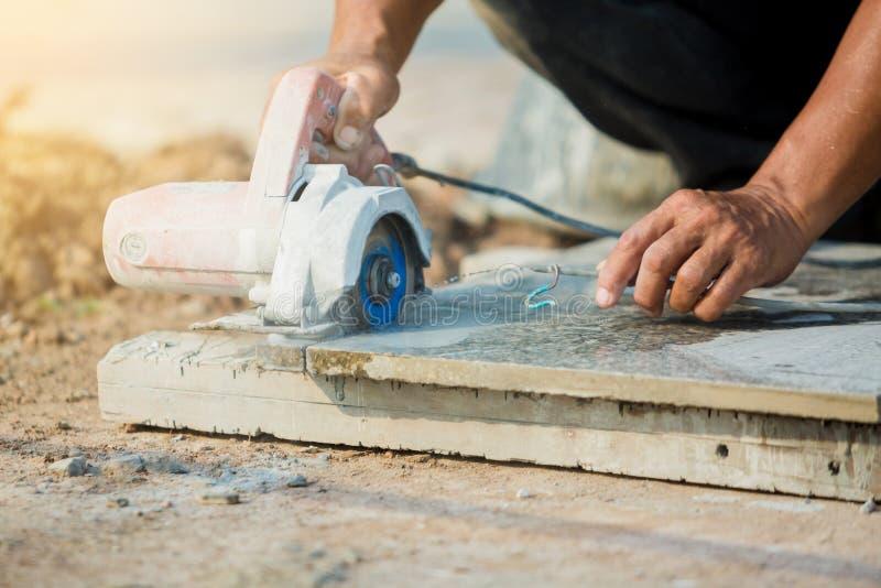 Trabajador que corta la piedra del granito con una hoja de sierra del diamante y un agua eléctricas del uso para prevenir el polv fotografía de archivo libre de regalías