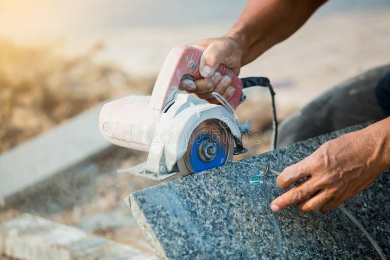 Trabajador que corta la piedra del granito con una hoja de sierra del diamante y un agua eléctricas del uso para prevenir el polv fotos de archivo