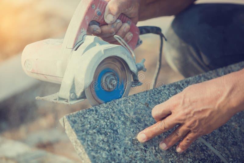 Trabajador que corta la piedra del granito con una hoja de sierra del diamante y un agua eléctricas del uso para prevenir el polv imagenes de archivo