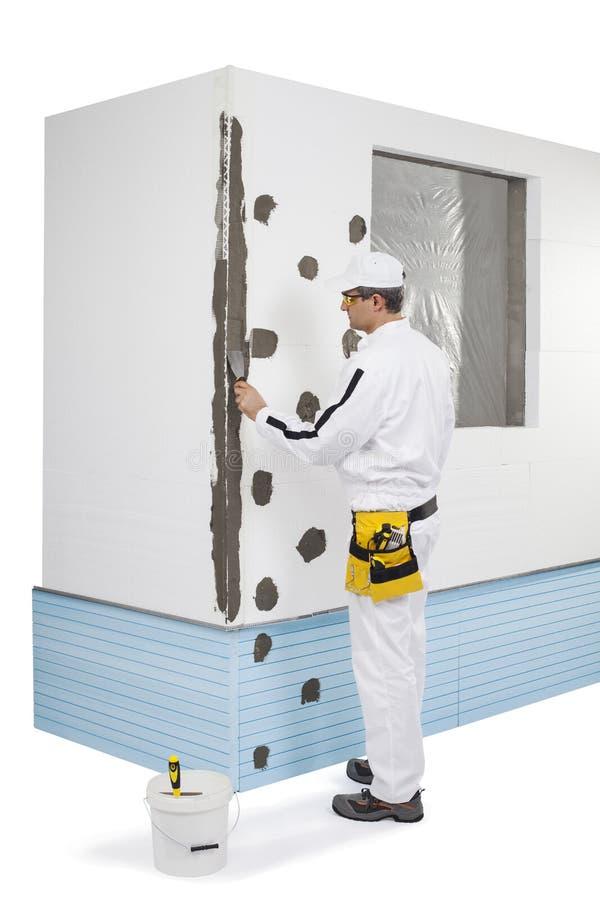 Trabajador que cubre un esquina-listón con una masilla