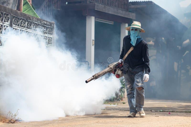 Trabajador que empaña la sustancia química para eliminar el mosquito en la calle fotos de archivo libres de regalías