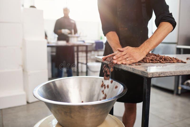 Trabajador que empuja granos de cacao en un cuenco para la fabricación de chocolate imágenes de archivo libres de regalías