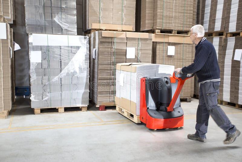 Trabajador que empuja la acción en Handtruck imágenes de archivo libres de regalías