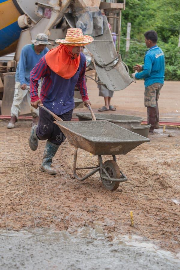 Trabajador que empuja la carretilla con el cemento mojado a verter el piso concreto fotos de archivo libres de regalías