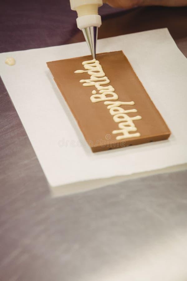 Trabajador que escribe feliz cumpleaños con el bolso aflautado en placa del chocolate fotos de archivo