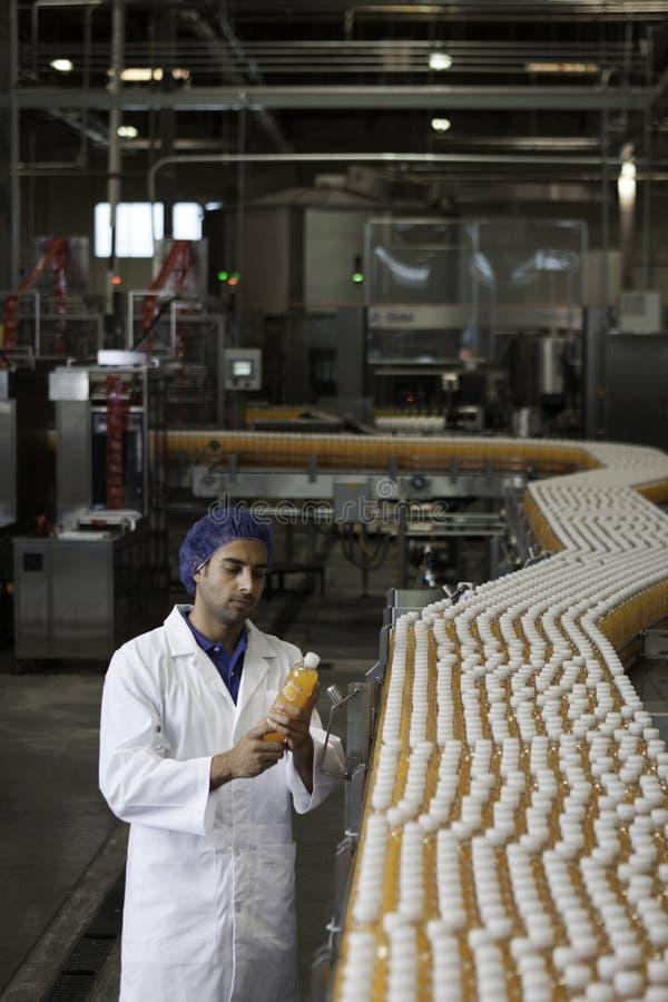Trabajador que examina la botella del zumo de naranja en la planta de embotellamiento imagen de archivo