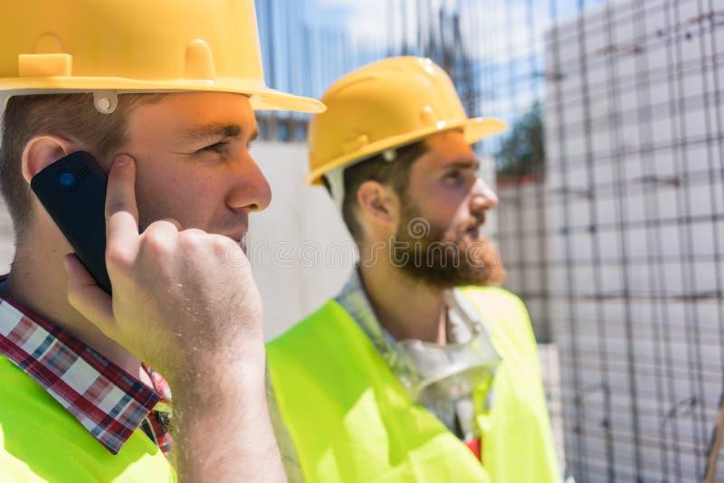 Trabajador que habla en el teléfono móvil durante trabajo sobre la construcción s imagen de archivo