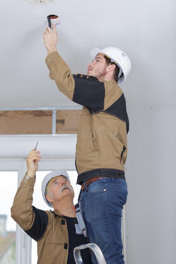 Trabajador que hace el agujero en el techo para la luz fotos de archivo libres de regalías