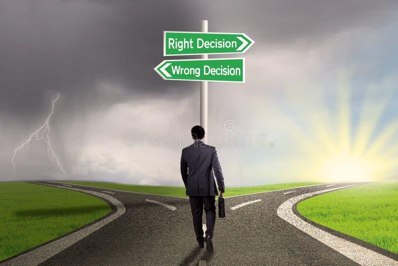 Trabajador que hace frente a dos opciones en el camino imagen de archivo