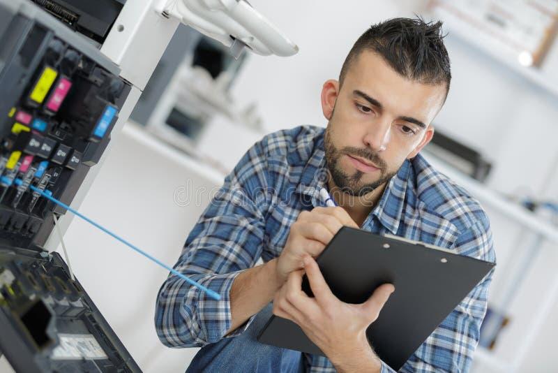 Trabajador que hace informe técnico sumario imagen de archivo libre de regalías