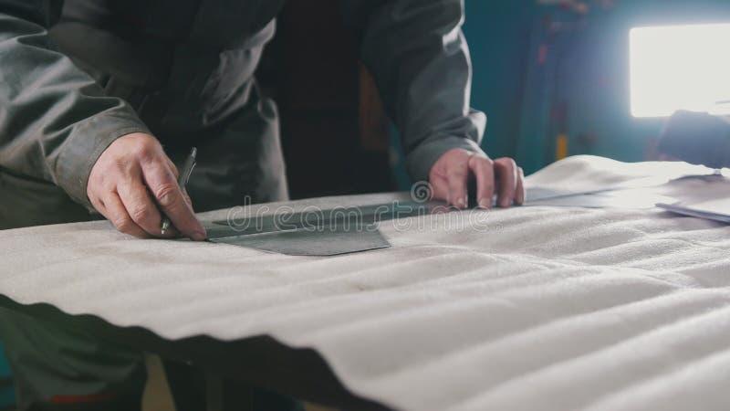 Trabajador que hace medidas y marcas en una pieza mediante una regla fotografía de archivo