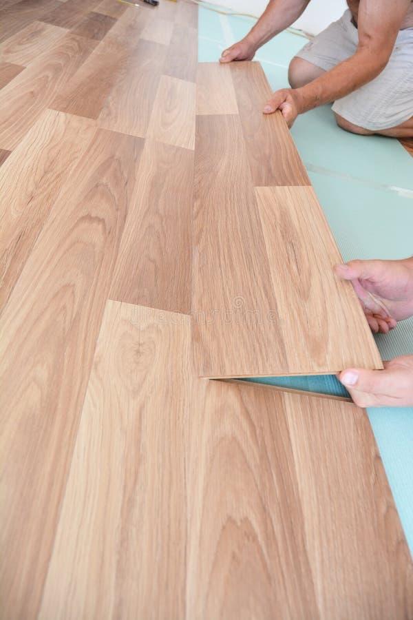Trabajador que instala el suelo laminado de madera foto de archivo