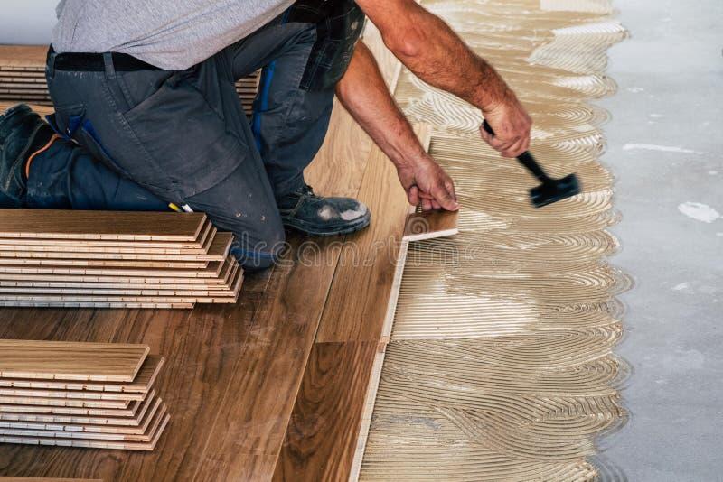 Trabajador que instala los tableros de suelo de madera foto de archivo
