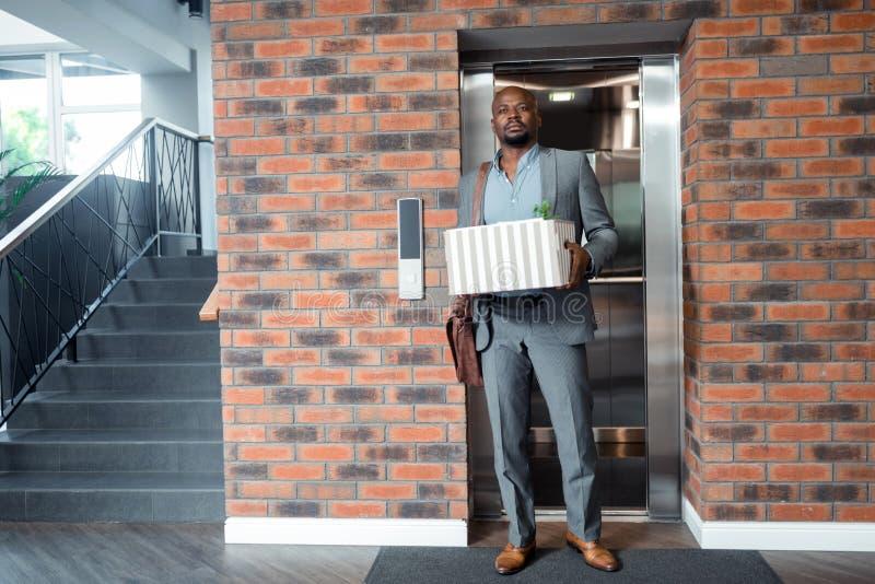 Trabajador que lleva la situación gris del traje en elevador después de encendido fotos de archivo