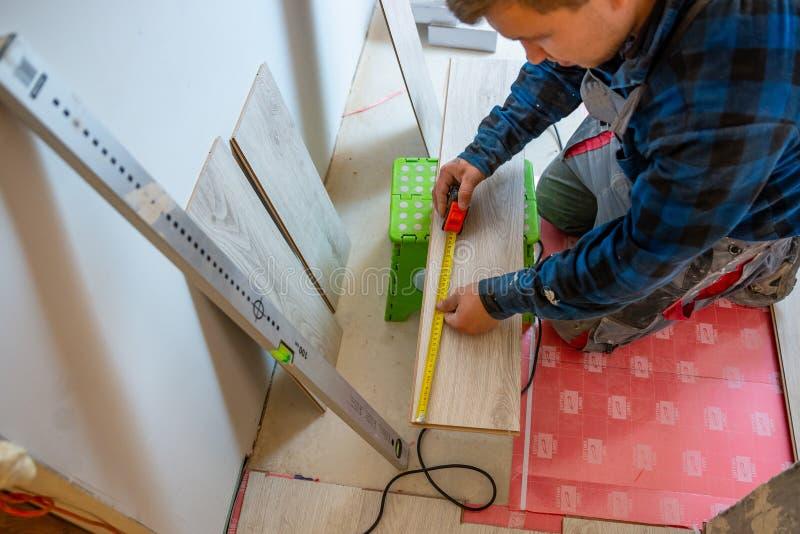 Trabajador que mide con el panel de piso de la lamina de la cinta métrica foto de archivo