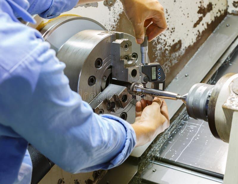 Trabajador que mide el metro micro ny de torneado de la pieza del CNC fotografía de archivo libre de regalías