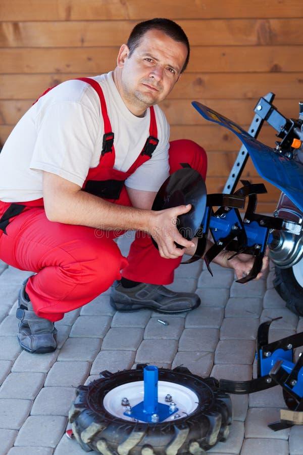 Trabajador que monta el accesorio de labranza en un cultivador fotografía de archivo libre de regalías
