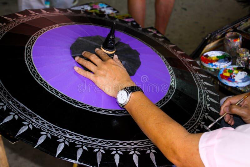 Trabajador que pinta un paraguas de papel en Chiang Mai, Tailandia imagenes de archivo