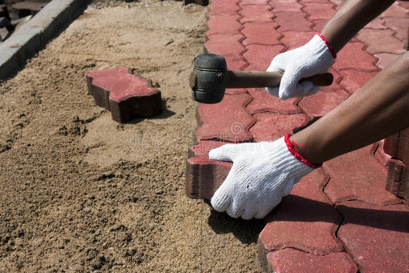 Trabajador que pone bloques de pavimentación concretos rojos. foto de archivo libre de regalías