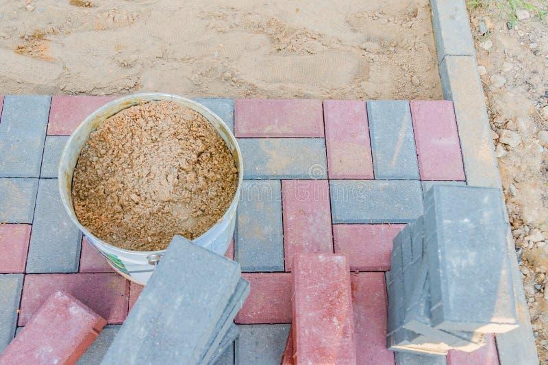 Trabajador que pone bloques de pavimentación concretos rojos y grises Camino que pavimenta, construcci?n imagen de archivo libre de regalías