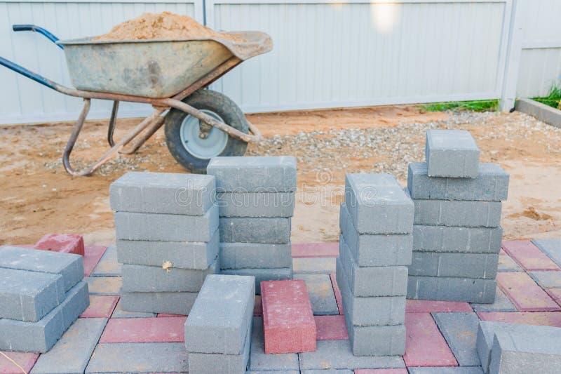 Trabajador que pone bloques de pavimentación concretos rojos y grises Camino que pavimenta, construcci?n foto de archivo