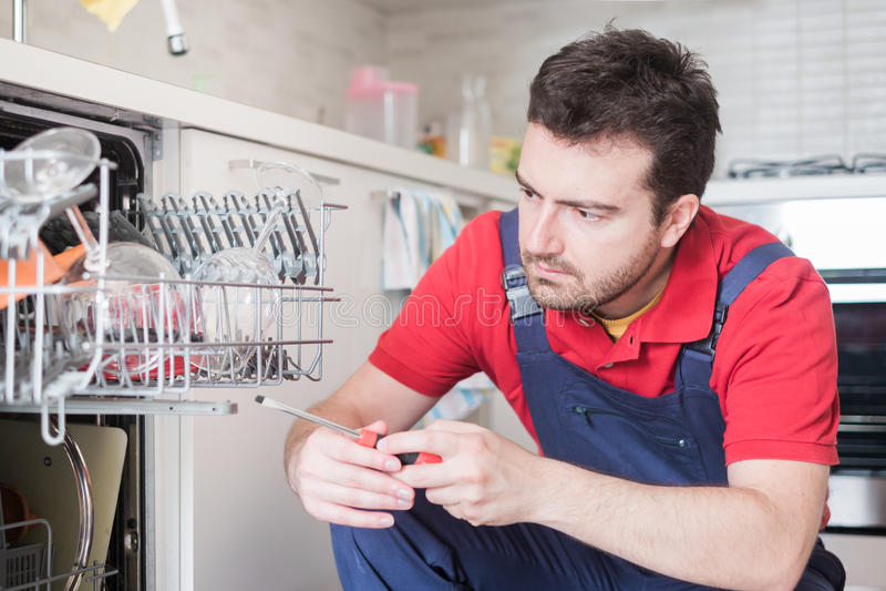 Trabajador que repara el lavaplatos en la cocina fotografía de archivo