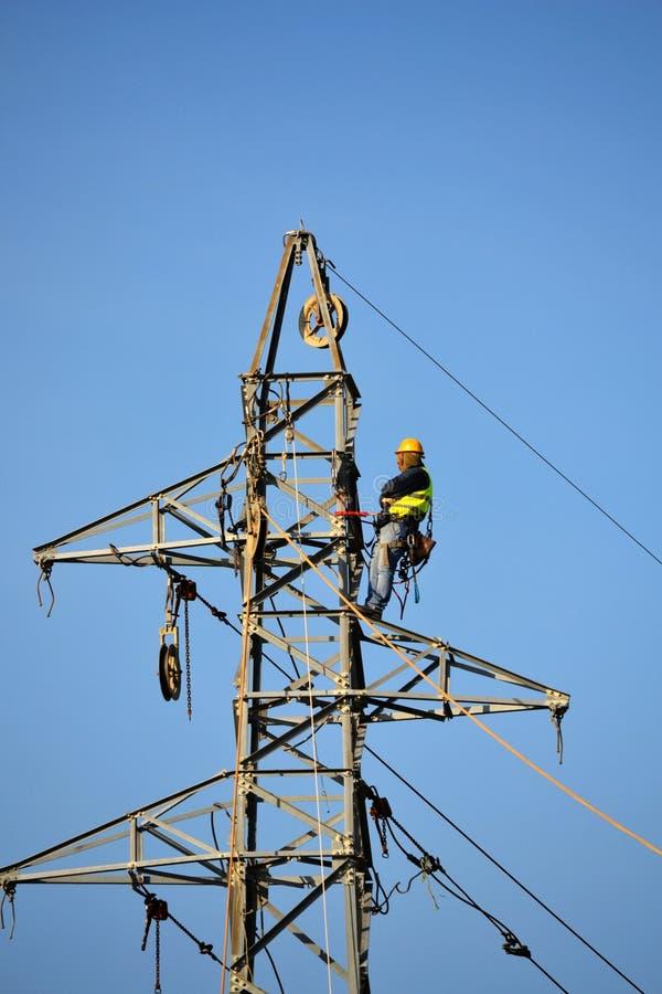 Trabajador que repara líneas eléctricas aéreas fotos de archivo