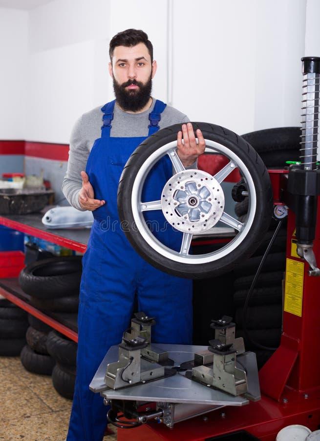 Trabajador que repara la rueda imagenes de archivo